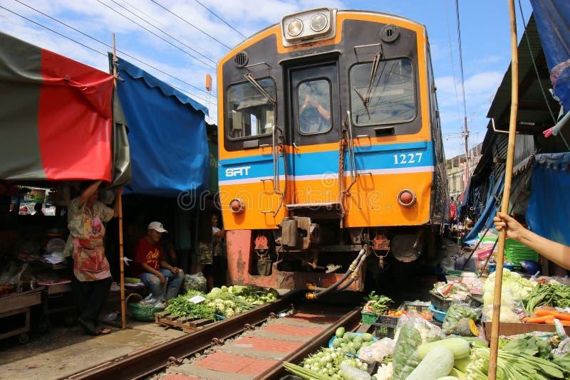 训练审阅Maeklong菜卖主在铁路轨道旁边使用他们的商品的火车市场,一个独特的市场 库存照片
