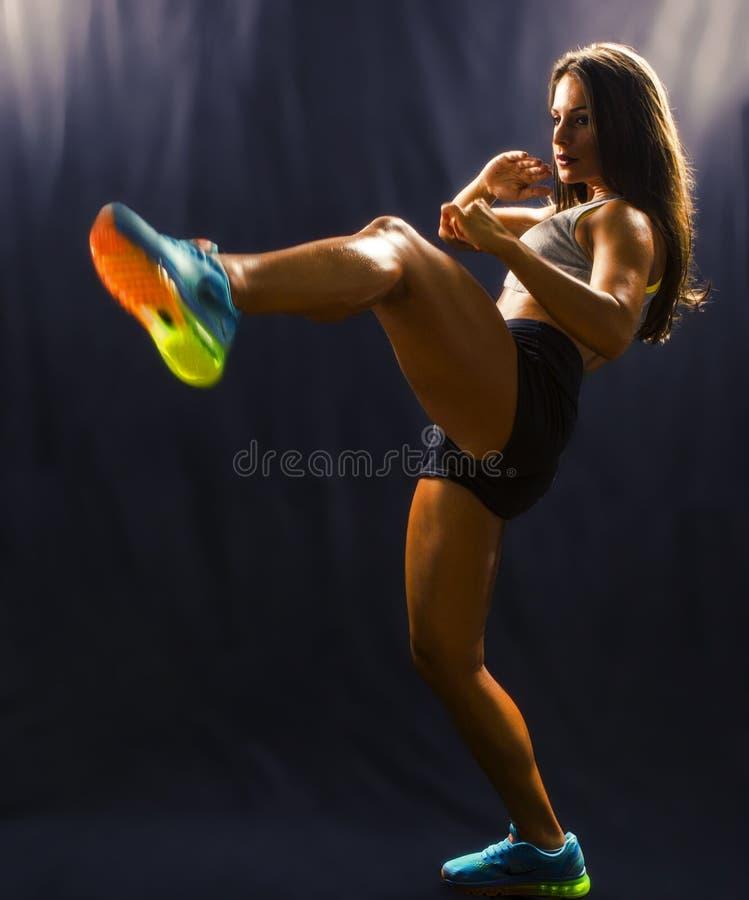 训练武术的坚强的体育妇女 免版税库存图片