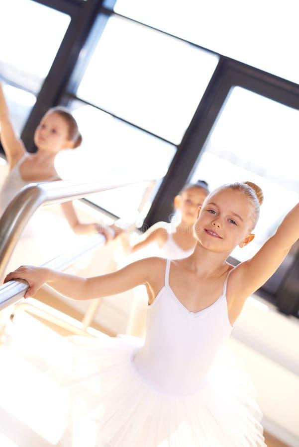 训练的相当微笑的年轻芭蕾舞女演员 图库摄影