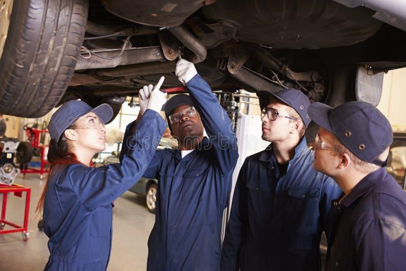 训练老师帮助的学生是汽车修理师 库存图片