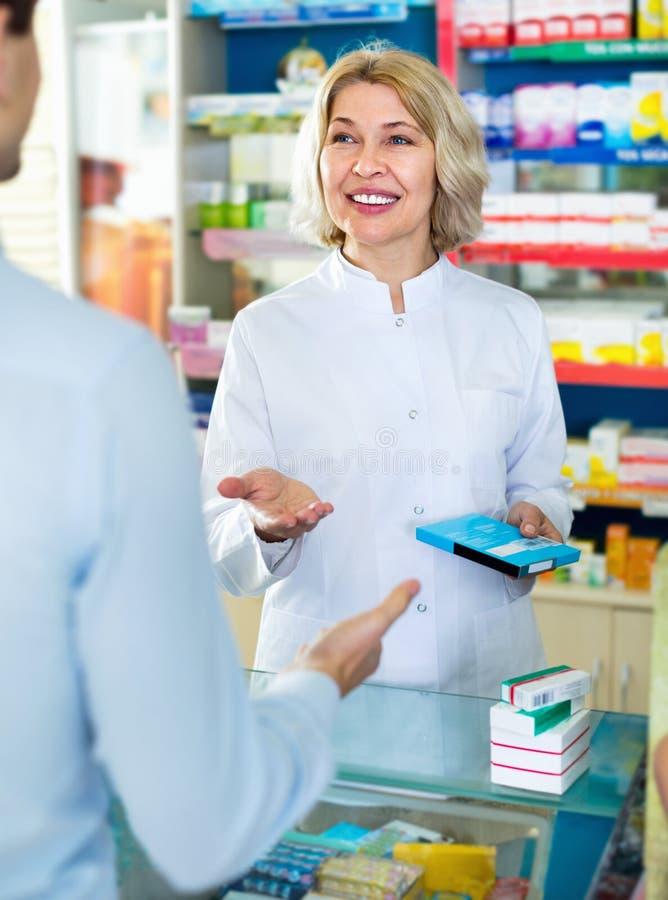 建议女性的药剂师关于药物用法的顾客 库存图片