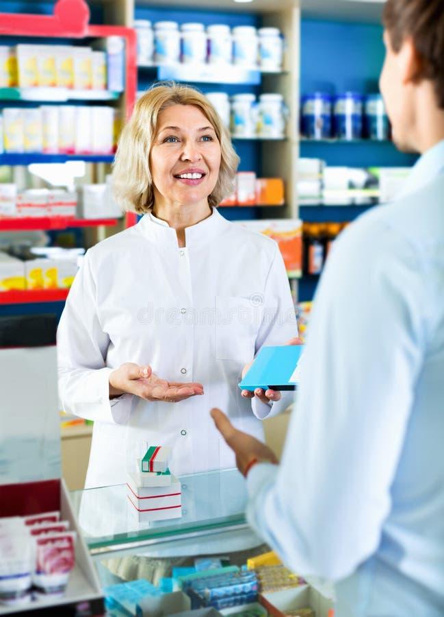 建议女性的药剂师关于药物用法的顾客 免版税库存图片