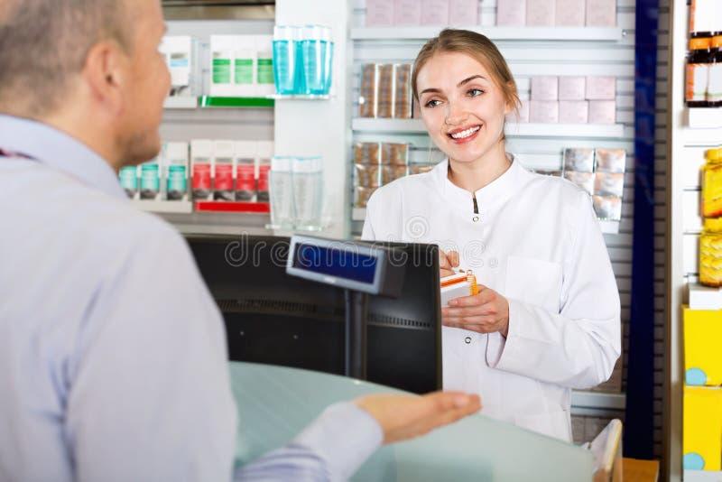 建议微笑的女性的药剂师关于药物用法的顾客 库存图片