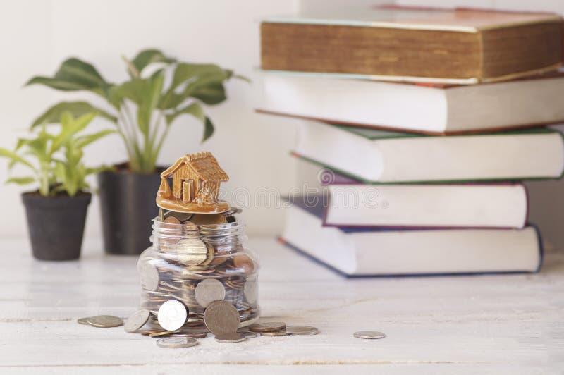 议院有在桌上的硬币、植物和书背景 免版税库存图片