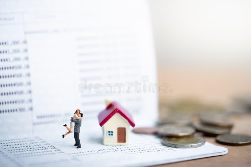 议院模型和小夫妇形象在站立的爱在银行存款簿 免版税库存图片