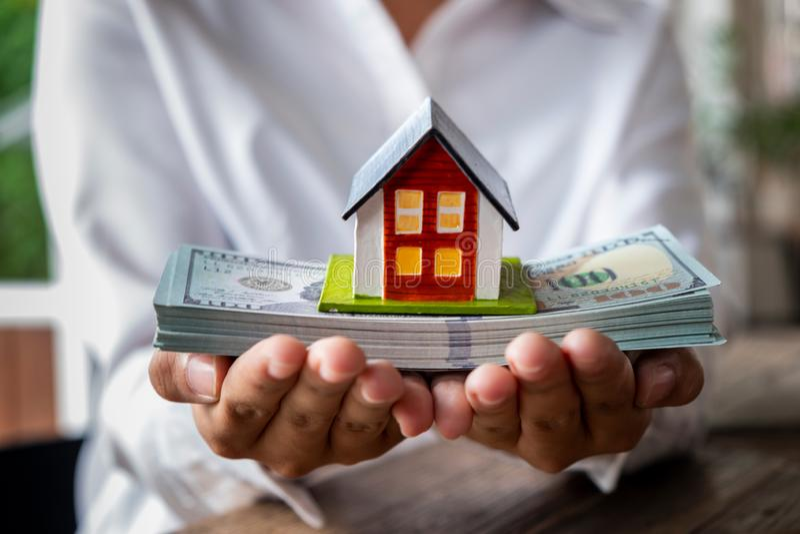议院模型和金钱在手中 免版税库存图片