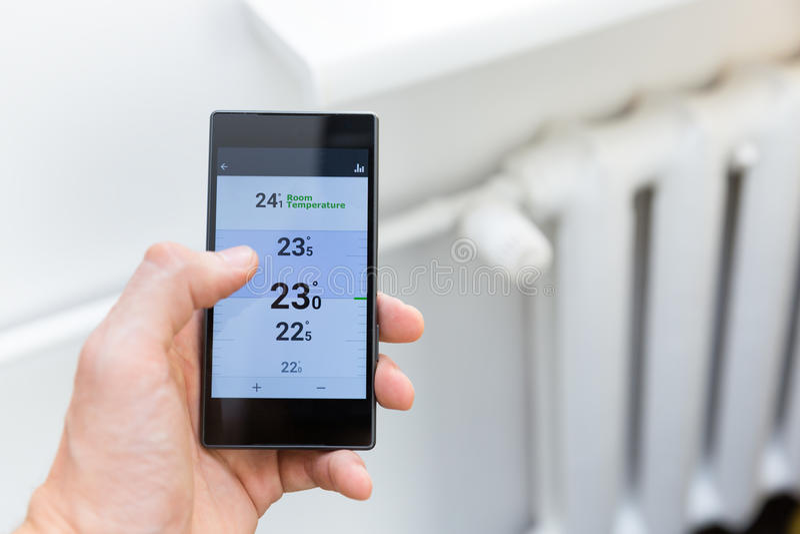 议院热化与巧妙的电话的温度控制系统 免版税库存图片