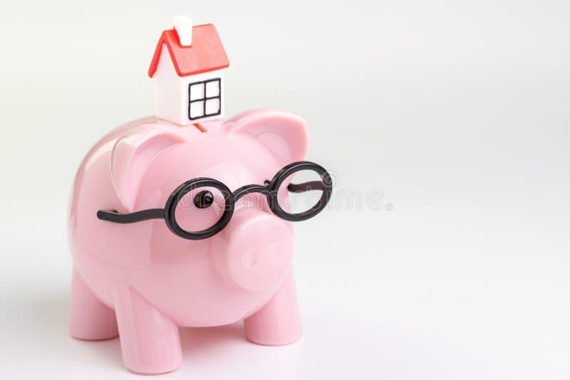 议院维护预算、费用、储款或者抵押房屋贷款概念,桃红色存钱罐戴着眼镜的微型房子在白色 库存图片