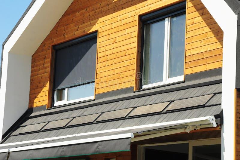 议院蒙蔽太阳保护外部与太阳电池板 在新的现代被动议院顶楼门面木墙壁的Windows有快门的 库存图片