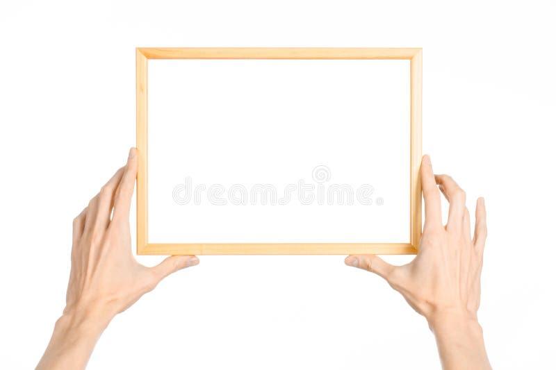 议院装饰和照片框架题目:拿着一个木画框的人的手被隔绝在演播室冷杉的白色背景 免版税图库摄影