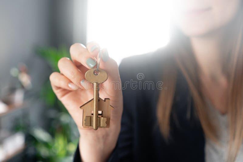 议院钥匙在手指在妇女手上转动 年轻俏丽的妇女微笑 现代轻的大厅内部 r 免版税图库摄影