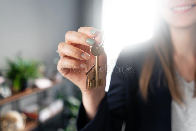 议院钥匙在手指在妇女手上转动 年轻俏丽的妇女微笑 现代轻的大厅内部 r 库存图片