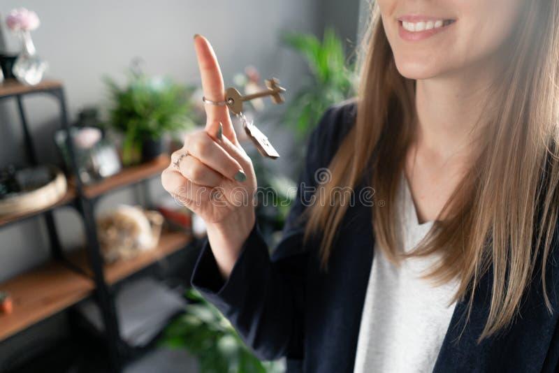 议院钥匙在手指在妇女手上转动 年轻俏丽的妇女微笑 现代轻的大厅内部 r 图库摄影