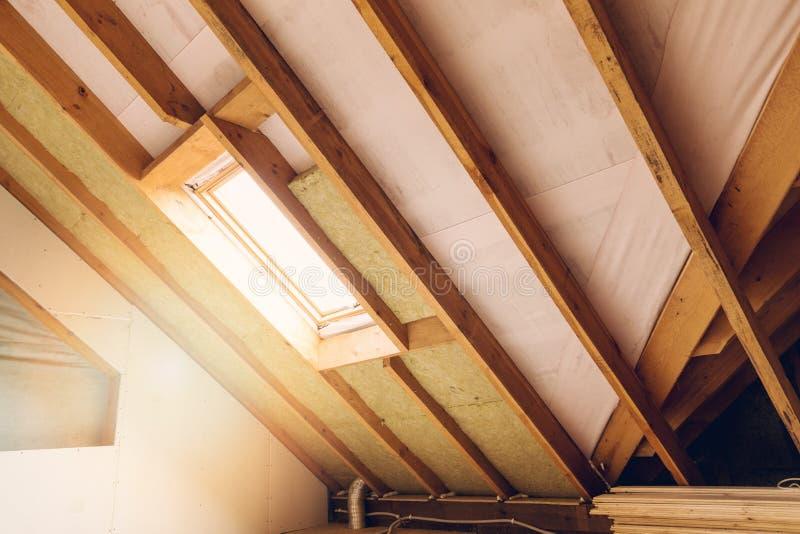 议院顶楼建设中有双重斜坡屋顶的房屋的绝缘材料 免版税库存照片