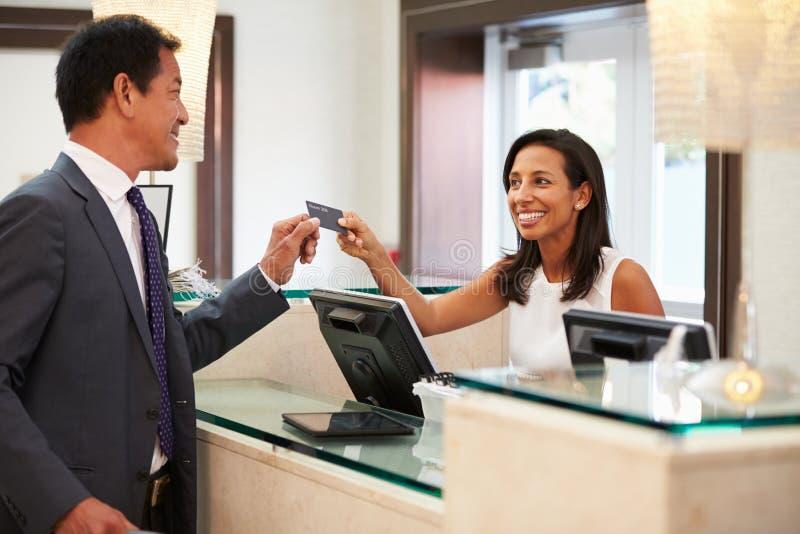 登记在旅馆招待会服务台的商人 免版税图库摄影