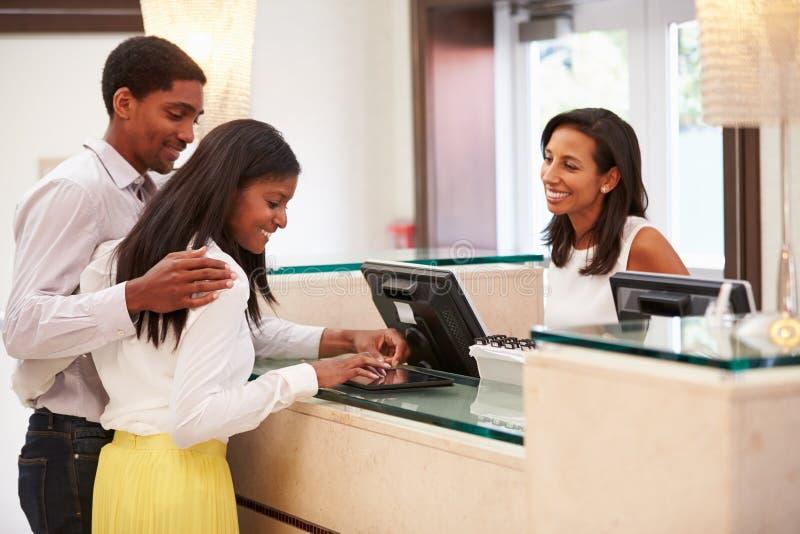 登记在旅馆招待会的夫妇使用数字式片剂 库存图片