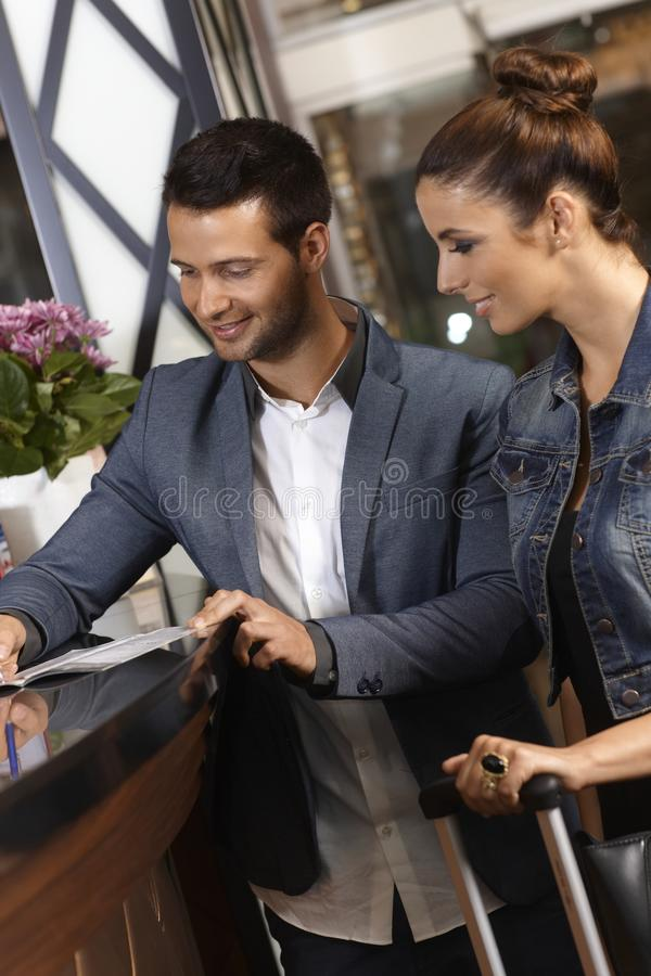 登记在旅馆招待会的年轻夫妇 免版税库存照片