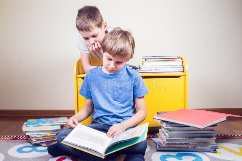 登记孩子读 男孩在家读一个故事给他的兄弟 免版税库存照片