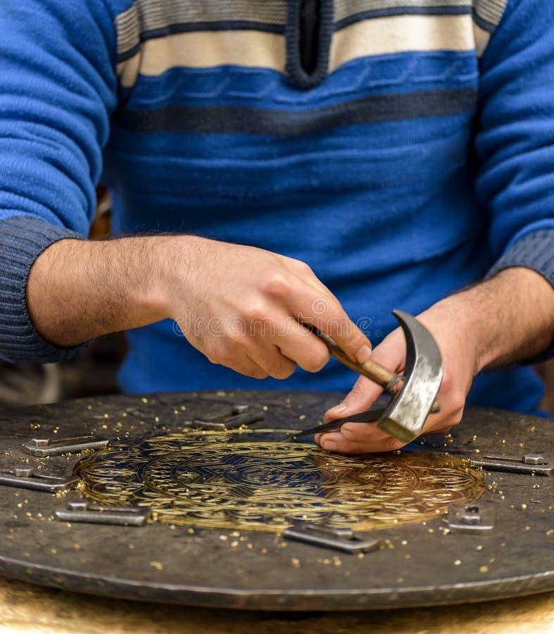 刻记黄铜名牌的工匠的手 免版税库存图片
