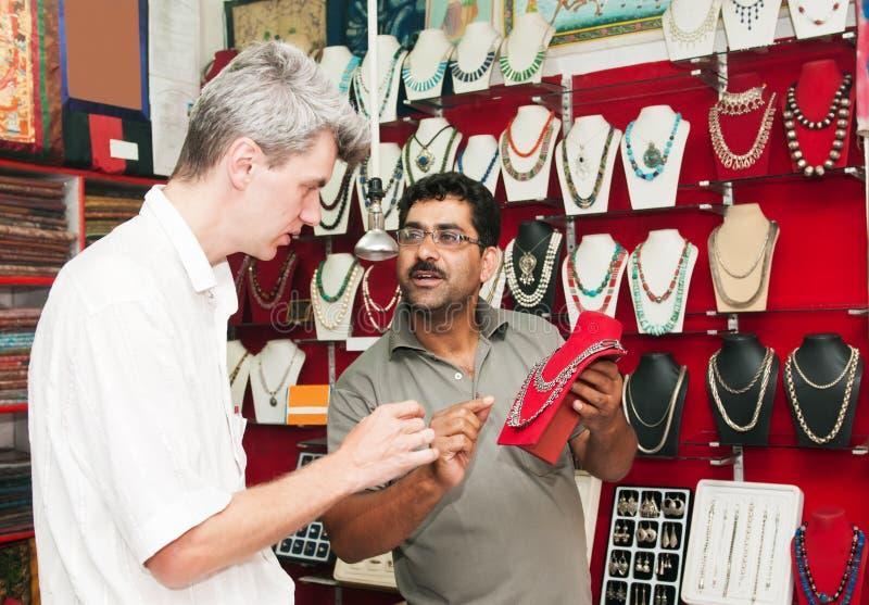 讲价在印第安金银手饰店的男 免版税图库摄影