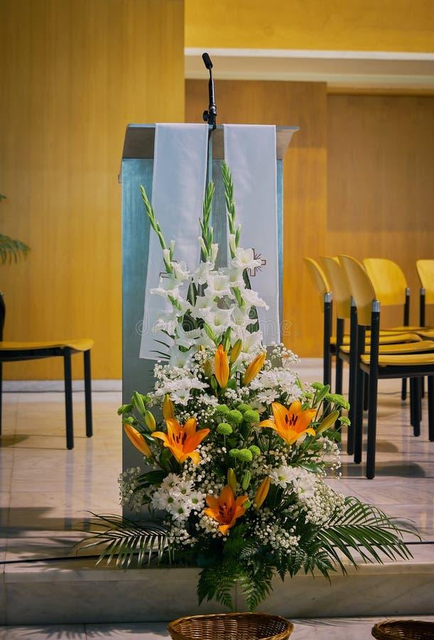 讲坛& x28的特写镜头;ambon& x29;在有花装饰的一个现代天主教会里在前景 库存照片