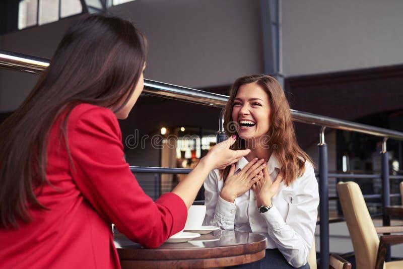 讲悦目的女性滑稽可笑的故事,当享用咖啡时 库存照片