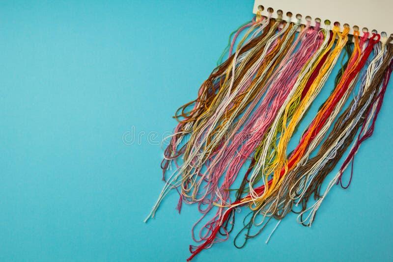 讲故事螺纹和编织样品彩色组在蓝色镶边背景 免版税库存照片