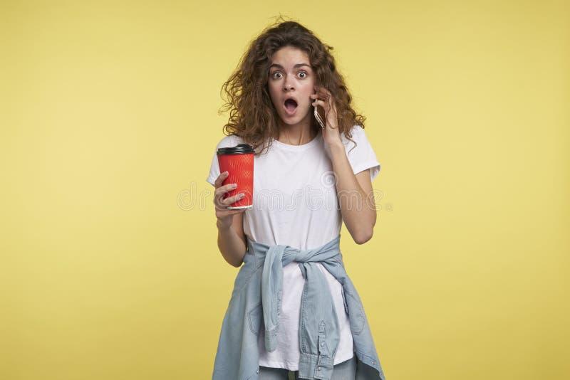 讲话由智能手机和拿着一杯咖啡的妇女, 免版税库存图片