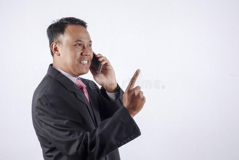 讲年轻的商人手机,隔绝在白色背景 免版税图库摄影
