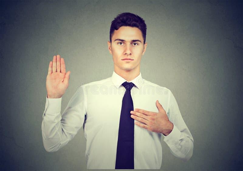 许下誓言诺言的英俊的年轻商人在灰色背景 免版税库存照片