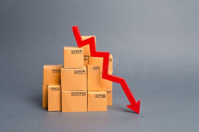 许多下来纸板箱和一个红色箭头 在工业生产,销售的概念下降下跌 经济不景气 免版税库存图片