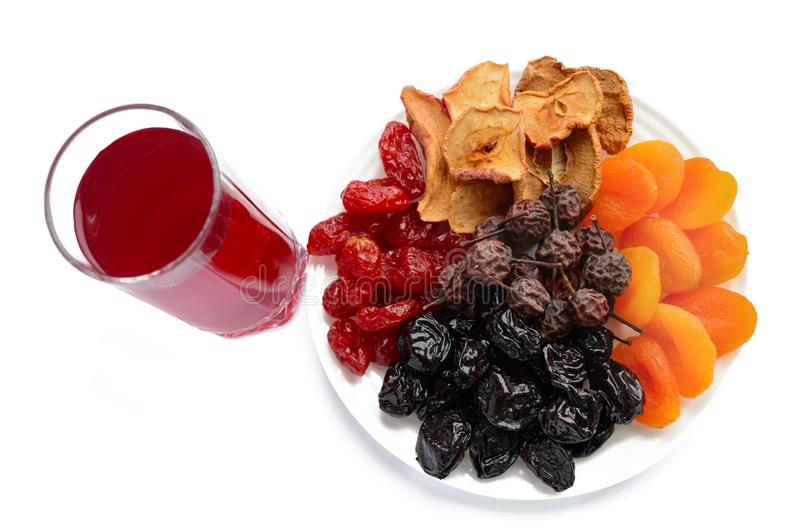 许多不同的干果子杏干、苹果、梨、修剪在一块白色板材和一杯蜜饯 免版税库存照片