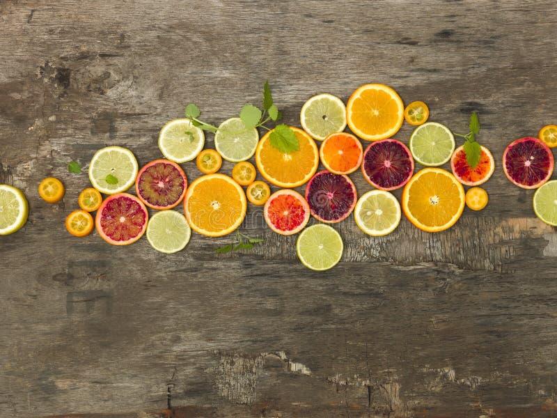 许多不同的水多和健康柑橘水果在老,葡萄酒木头背景一起说谎 库存图片