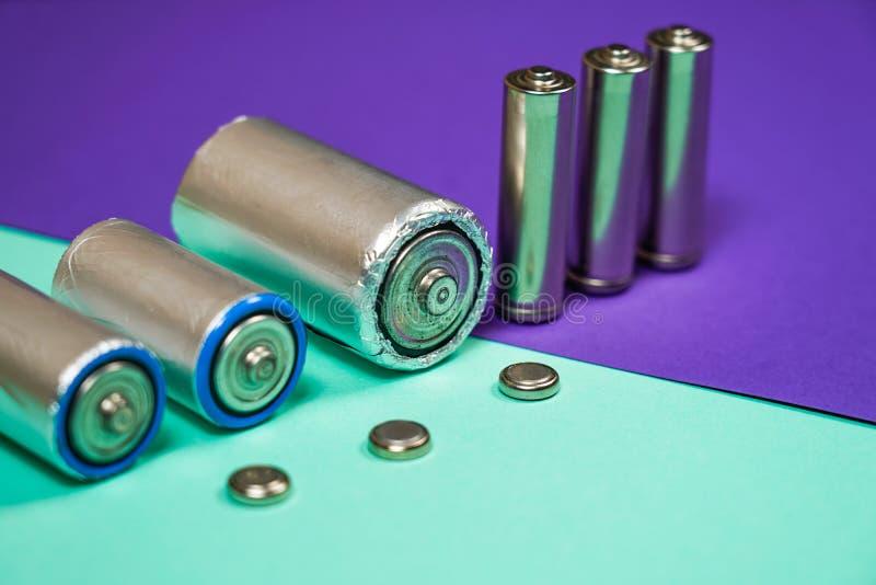 许多不同的类型使用的或新的电池,可再充电的累加器,在颜色背景的碱性电池 免版税图库摄影