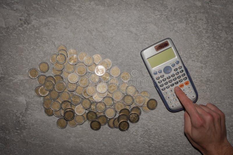 许多与计算器的欧元硬币 硬币背景  典型的图象在家庭储款 库存照片