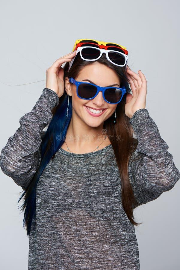 戴许多五颜六色的太阳镜的微笑的妇女 图库摄影