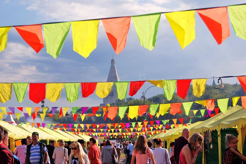 许多五颜六色的旗子 在旗子下的许多人民步行 免版税图库摄影
