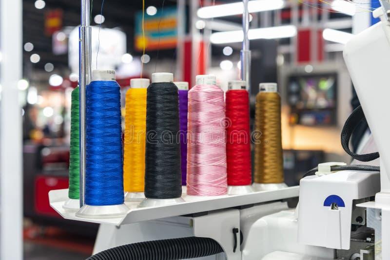 """许多五颜六色的棉花卷轴螺纹被设定在纺织品â€的现代和自动高技术缝合或刺绣机器"""" 库存照片"""