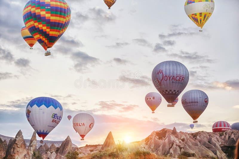 许多五颜六色的气球离开入天空在黎明 在大美丽的气球的所有天空 山的美妙的风景 库存图片