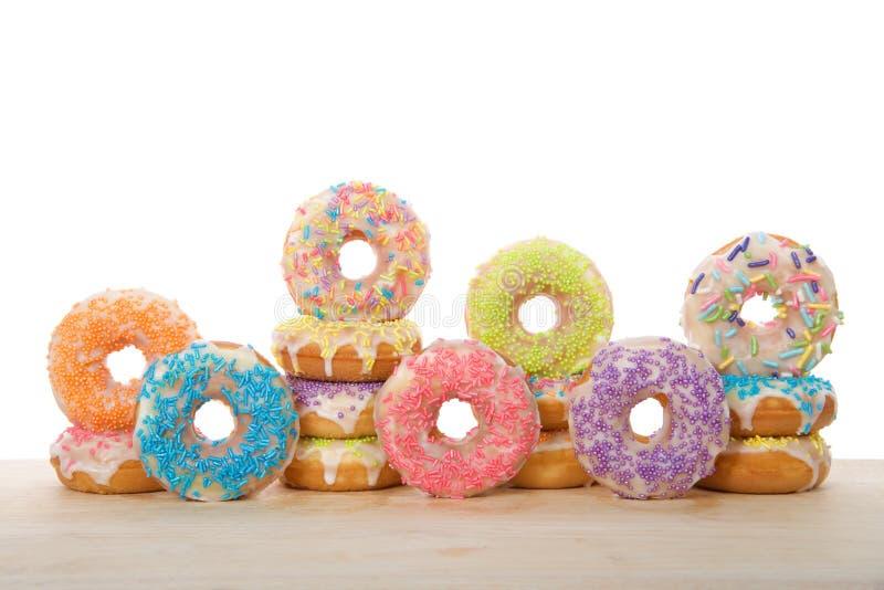 许多五颜六色的糖果涂上了在被隔绝的一张轻的木桌上的油炸圈饼 库存图片