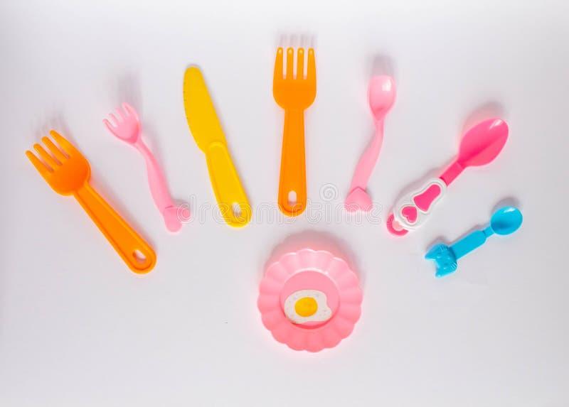 许多五颜六色的plasic叉子、匙子和刀子在白色背景与拷贝空间,顶视图 婴儿食品的设备 免版税库存照片