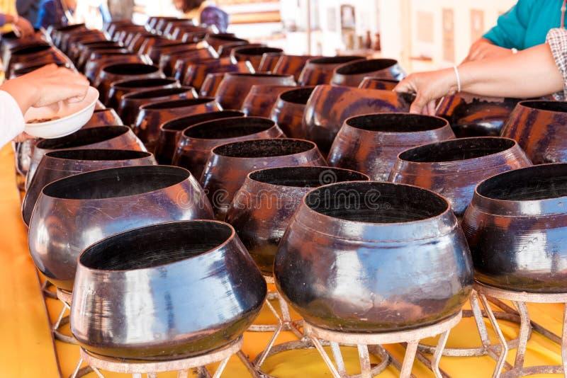 许多人民铸造下来到修士的施舍碗 免版税库存图片