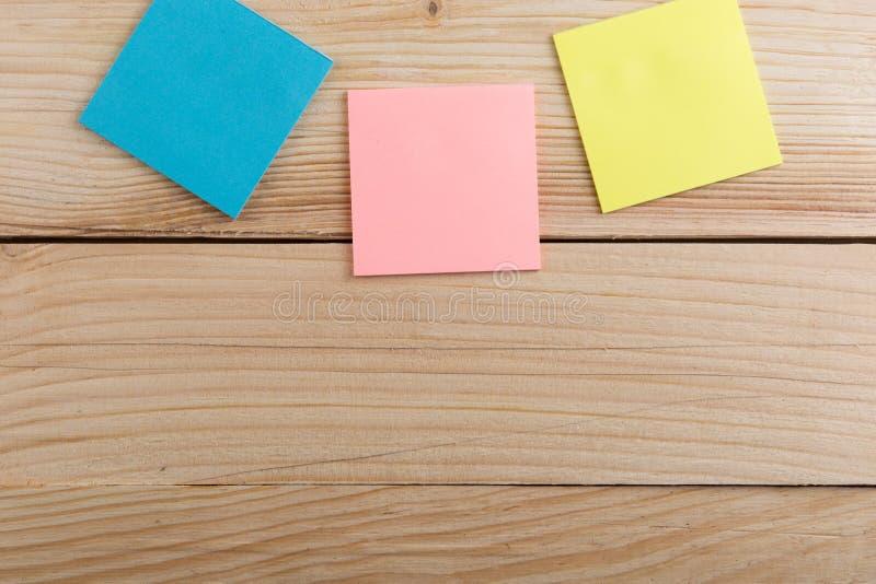 许多关于木书桌的五颜六色的稠粘的笔记 r 免版税库存图片