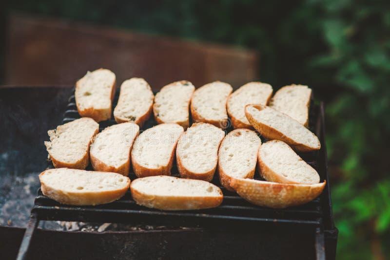 许多切片在一个格栅的烤长方形宝石面包在新鲜空气的火 免版税图库摄影