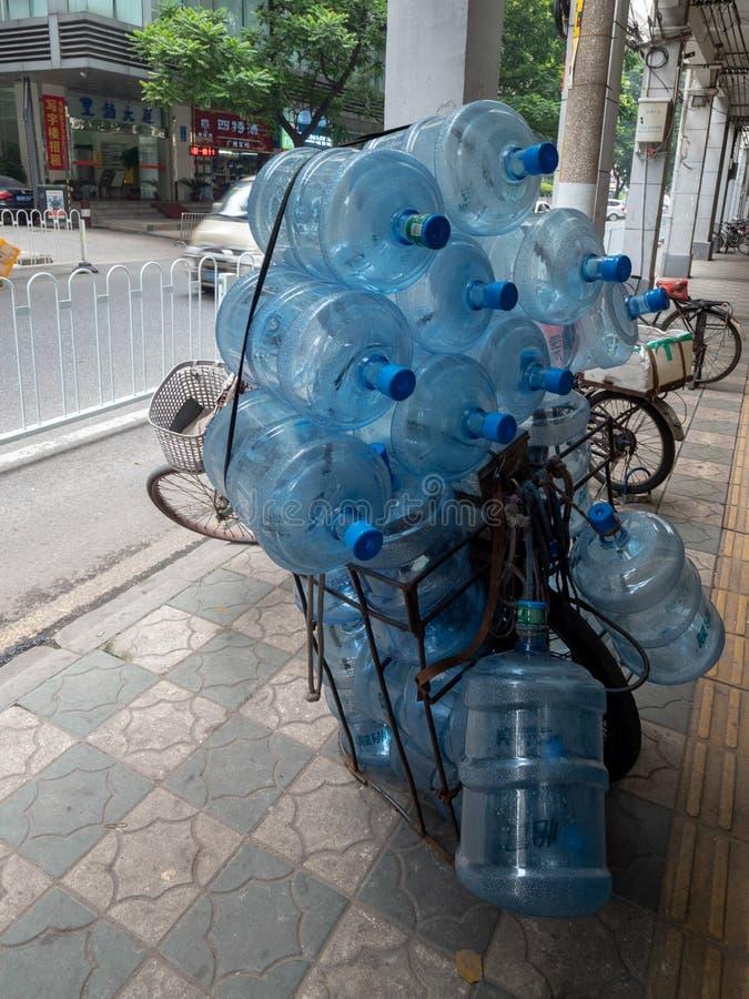 许多在一辆自行车的空的水罐头在广州,中国 库存照片
