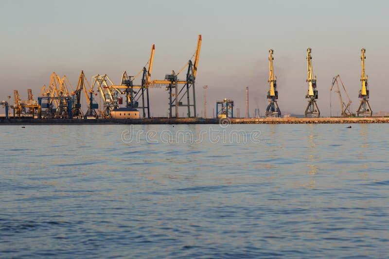 许多在口岸的大起重机剪影在日落金黄光  马里乌波尔,乌克兰 免版税库存照片