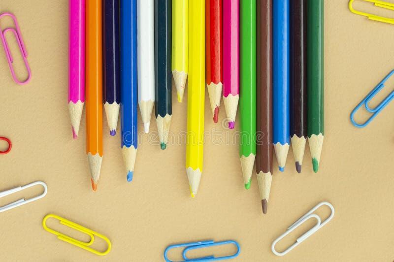 许多在好的米黄背景的五颜六色的铅笔和纸夹 免版税库存照片