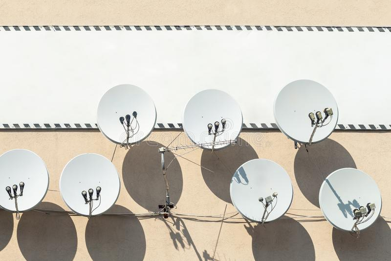 许多在有大白色空的牌横幅的修造的墙壁上垂悬的卫星盘天线在背景 文本的Copyspace 库存图片