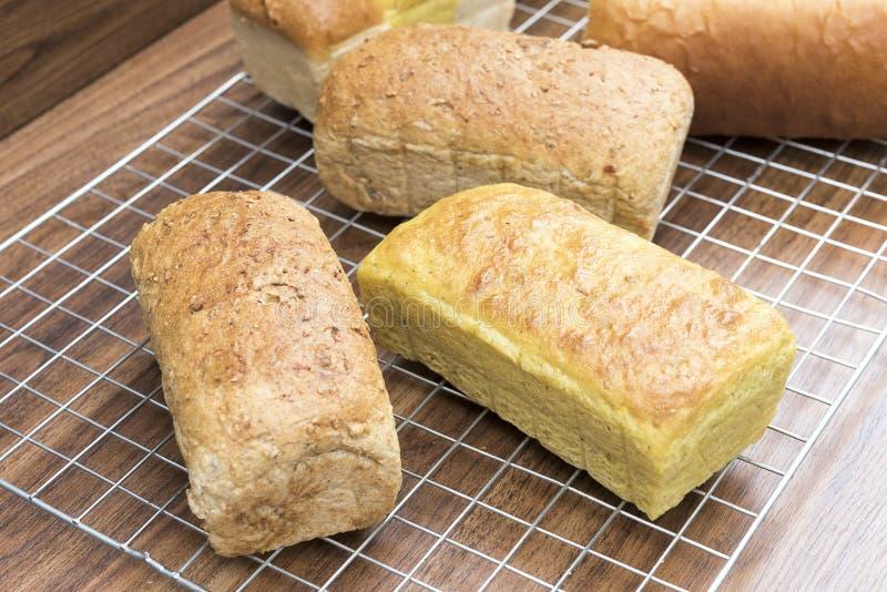 许多在木桌上的混杂的家制面包大面包 免版税库存图片