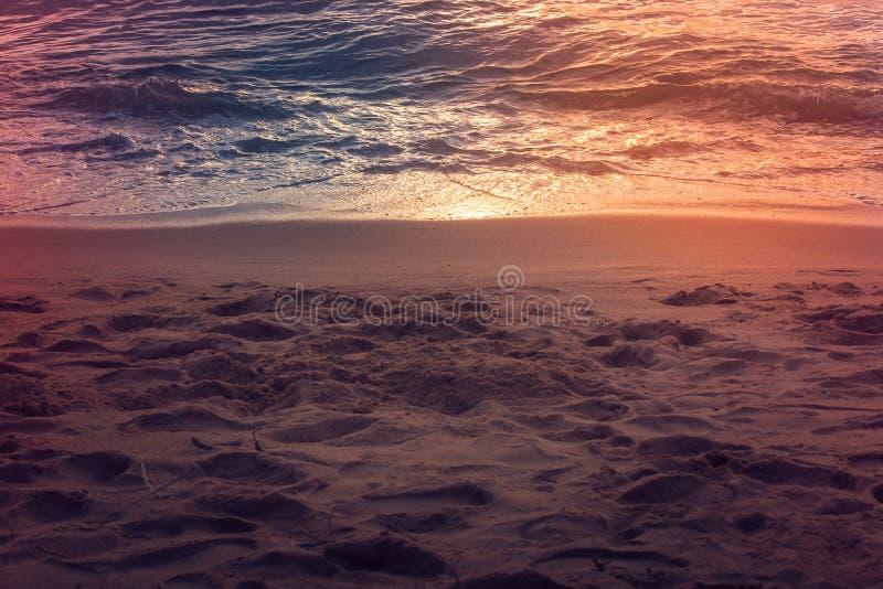 许多在沙子海滩的各种各样的脚印与日落光反射在暮色时间的海表面上 库存图片